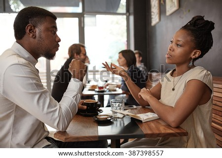 African woman and man discussing business ideas at busy cafe - stock photo