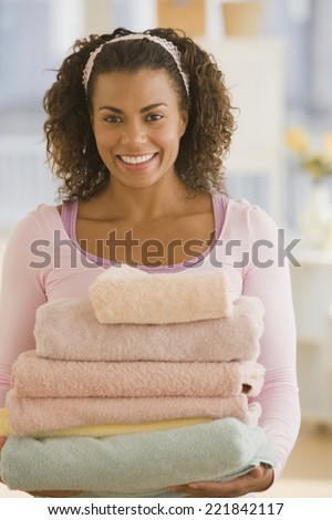 African woman carrying stack of towels - stock photo