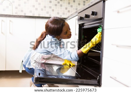 african woman cleaning stove in the modern kitchen - stock photo