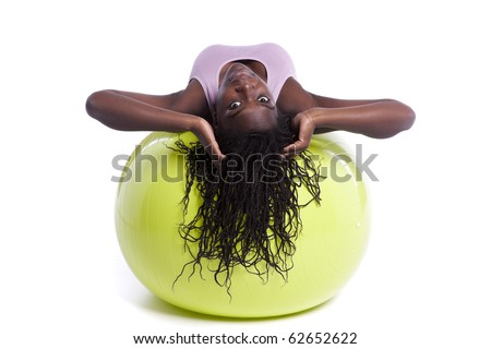 african woman exercising with a yellow pilate ball - stock photo