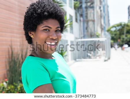 African woman in a green shirt in the city with buildings and street in the background - stock photo
