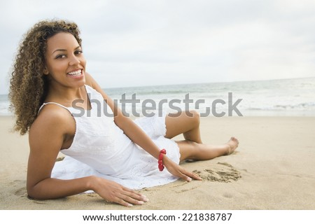 African woman laying on sand - stock photo