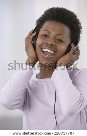 African woman listening to headphones - stock photo