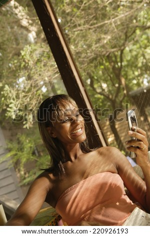 African woman looking at cell phone - stock photo