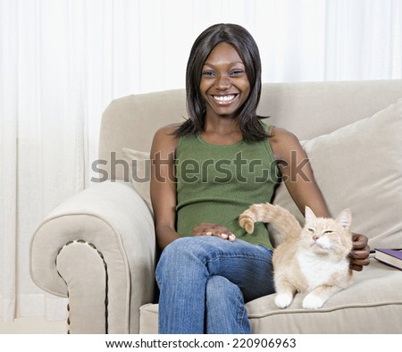 African woman petting cat on sofa - stock photo