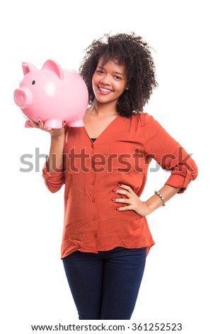 African woman putting some money into a piggy bank - stock photo