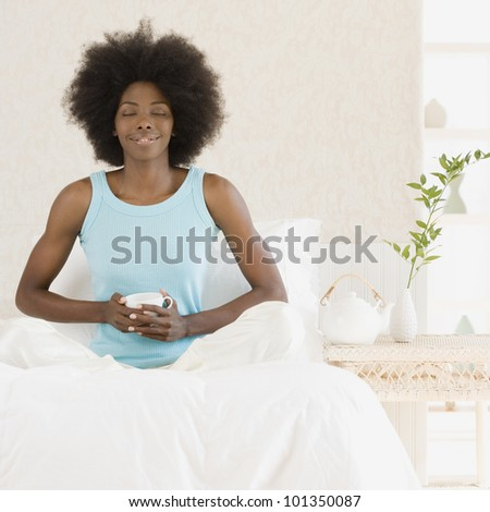 African woman relaxing on bed - stock photo