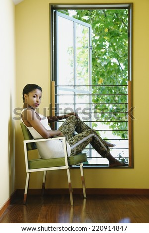 African woman sitting next to window - stock photo