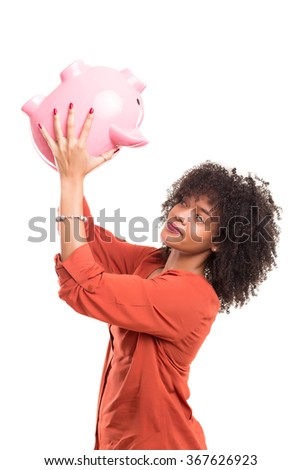 African woman trying to get some money out of a piggy bank - stock photo