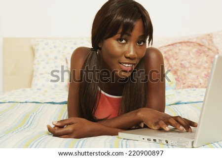 African woman typing on laptop in bed - stock photo
