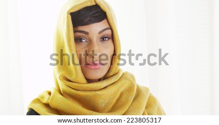 African woman wearing golden head scarf by window - stock photo