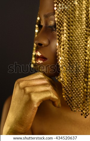 African woman with gold metallic make-up and full shiny lips, close up - stock photo