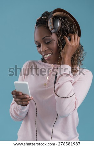 African woman with headphones listening music - stock photo
