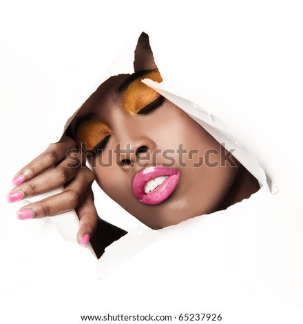 African woman with pink and yellow metallic make-up and full shiny lips - on the paper whole background - stock photo