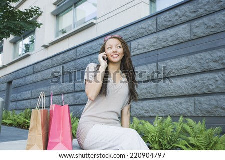 African woman with shopping bags talking on cell phone - stock photo
