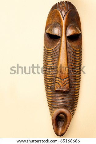 African Wooden Mask on Beige Background - stock photo