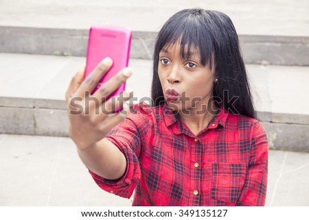 African young girl with mobile making photo