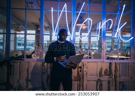 African young man standing in office using laptop computer. Business executive in office with big neon light work sign at the back on wall. - stock photo