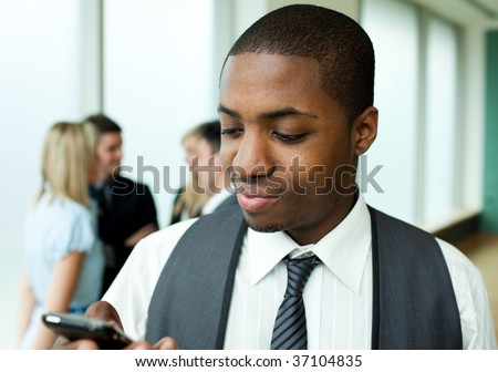Afro-American businessman sending a text in office - stock photo