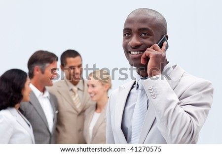 Afro-American businessman talking on mobile phone with his team in the background - stock photo