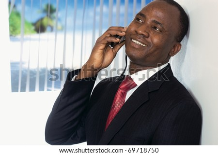 Afro-American businessman talking on phone in the office - stock photo