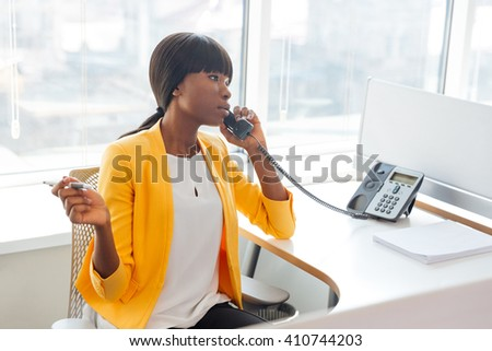 Afro american businesswoman talking on the phone in office - stock photo