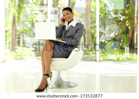 Afro American businesswoman using laptop and smartphone in a lobby - stock photo