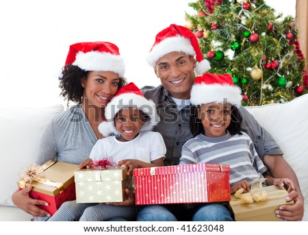Afro-American family holding Christmas presents at home - stock photo
