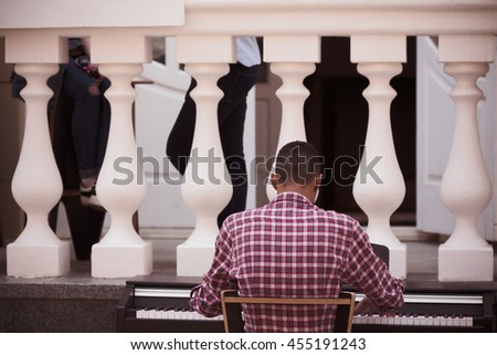 Afro-american man playing piano outdoors in city center. Professional musician playing piano. Closeup picture of of piano keyboard. - stock photo