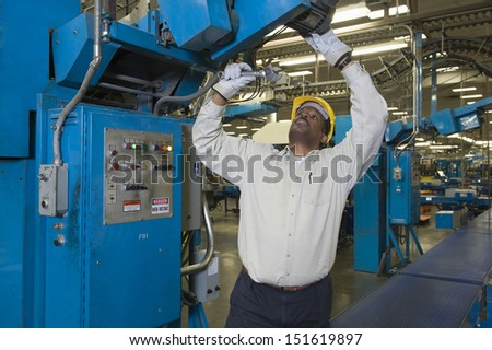 Afro American man working in newspaper factory - stock photo