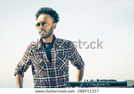 Afro american model artist ready to perform at dj console during spring break festival - Hipster funky disc jockey at summer beach party - Male trendy person with sunglasses at disco rave event - stock photo