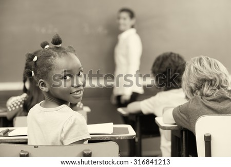 Afro american schoolgirl smiling during a lesson. - stock photo