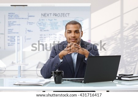 Afro american smiling confident businessman with laptop computer sitting at startup business office desk, looking at camera. - stock photo
