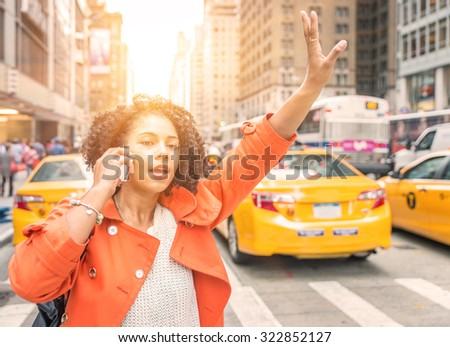 afro american woman calling a taxi in New York near Time square district. concept about urban life, people and transportation - stock photo