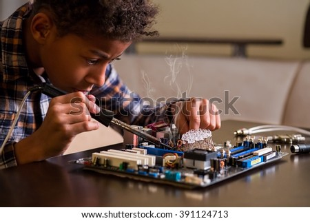 Afro boy fixing motherboard. Black kid repairs motherboard. Few touches here and there. Everything by the book. - stock photo