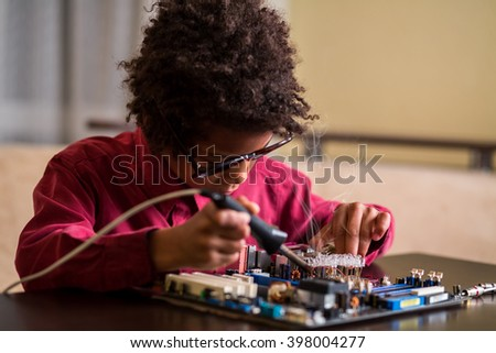 Afro boy soldering motherboard. Darkskinned boy solders motherboard. I know what to do. Very specific hobby. - stock photo