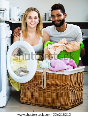 Afro husband and white housewife using washing machine indoors. Focus on woman - stock photo