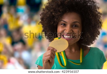 Afro woman holding a gold medal in the stadium - stock photo