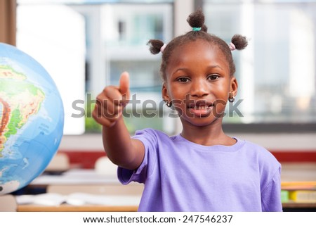 Afroamerican female student learning geography with thumbs up. - stock photo