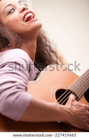afroamerican woman singing and playing guitar on her sofa in her living room - stock photo