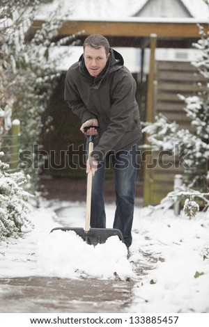 after a snowstorm. man with a black shovel to removes the snow from a house entrance. - stock photo