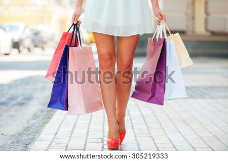 After day shopping. Close-up of young woman carrying shopping bags while walking along the street - stock photo