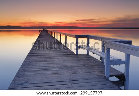 After sunset at Long Jetty, fiery red clouds and reflections in Tuggerah Lake, Central Coast NSW, Australia - stock photo