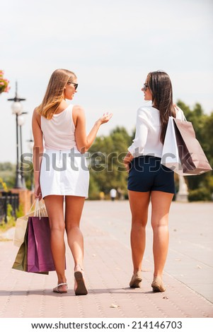 After the day shopping. Rear view of two beautiful young women with shopping bags walking by the street and talking - stock photo