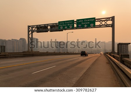 Afternoon Haze and air pollution on Ross Island Bridge with freeway signage in Portland Oregon due to forest wildfires - stock photo