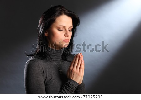 Afternoon shaft of light streams into room as beautiful young caucasian woman with eyes closed, has a quiet religious moment deep in prayer, wearing crucifix necklace. - stock photo