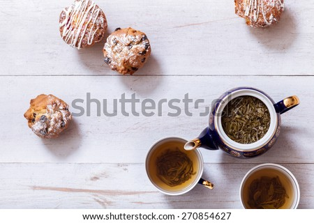 Afternoon tea with cakes on the table top view. Muffins on white  table with black tea. The Time of Tea Break.  - stock photo