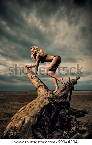 Afternoon woodclimbing. A woman climbing on driftwood on the beach. - stock photo