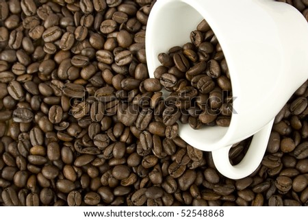 Against the backdrop of overturned white coffee beans from the cup and spilling coffee beans - stock photo