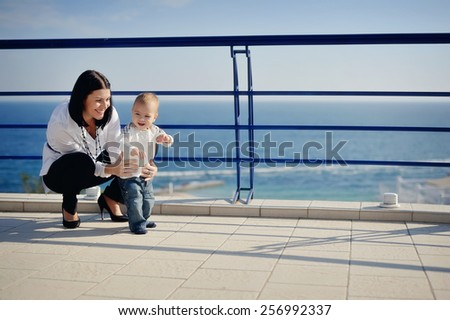against the backdrop of sea and sky mom plays with her young son - stock photo